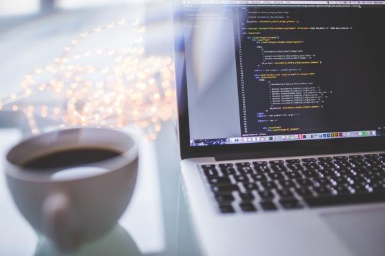 Syntolkning: Bärbar dator på ett bord. En kaffekopp till vänster om datorn.