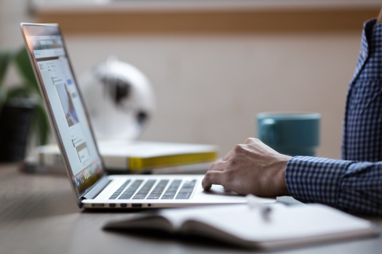 Syntolkning: En person sitter vid en bärbar dator.