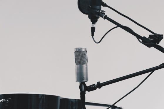 Syntolkning: Två mikrofoner, en svart och en silverfärgad, mot en vit bakgrund.