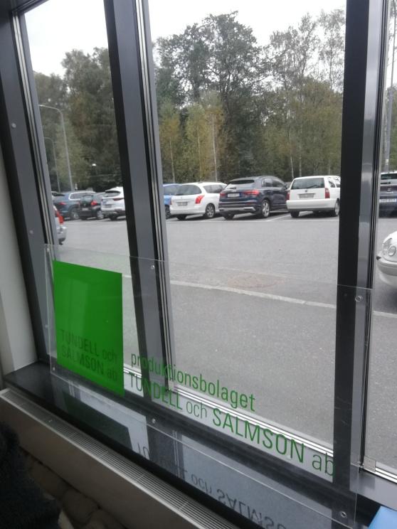 """Syntolkning: En grön skylt med texten """"Produktionsbolaget Tundell och Salmson AB"""" står i ett stort fönster med utsikt mot träd och bilar."""