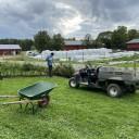 Deltagare som står vid traktor, grävkärra och odling.