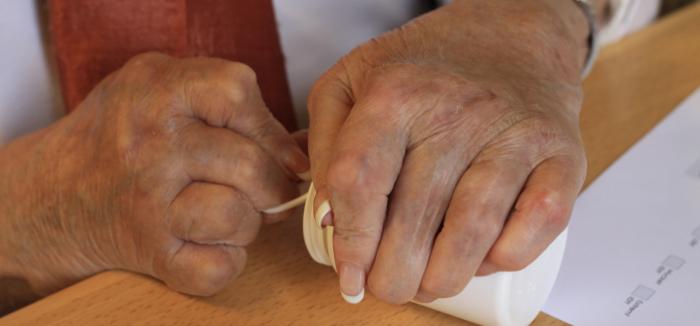 Syn-tolkning: En bild på en reumatisk persons händer som försöker öppna en vit medicinburk.