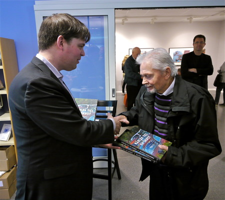 Staffan Ekengren överlämnade två böcker till bröderna Ivansson som äger bilskroten i Båstnäs. På bilden är det Rune Ivansson som tar emot böckerna.