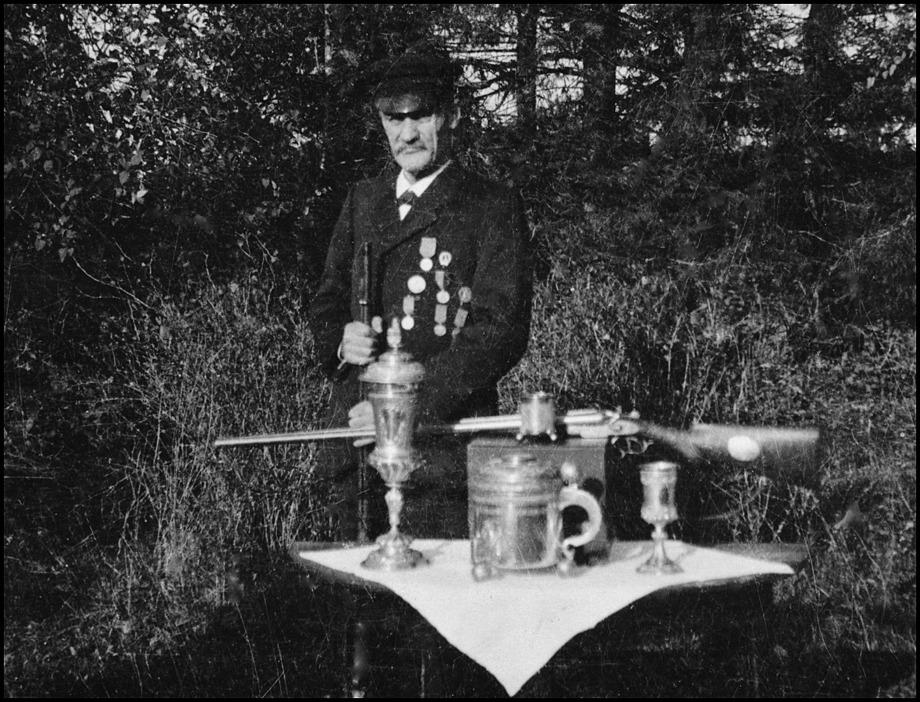 Storskytten Nils Aronsson Dusserud med sin prissamling. Dryckeskannan, dubbelbössan och 600:- i prispengar fick han vid riksskyttetävlingen i Stockholm 1897. Kort före sin död skänkte han hela sin förnämliga prissamling till Wermlands Skytteförbund. Nils Aronsson avled 1941.