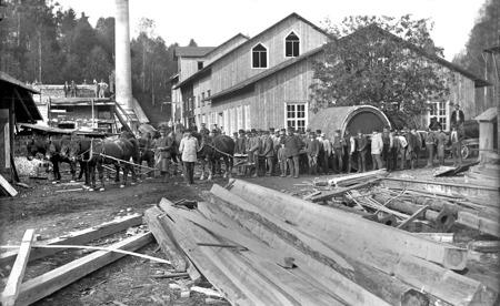 Efterfrågan på papper har ökat kraftigt och träsliperiet, som byggdes 1872 i Hån, byggs om till pappersbruk. På bilden anländer den nya papperscylindern, dragen av 8 hästar med 4 hästar bakom cylindern som broms i utförsbackarna. Mannen i den ljusgrå rocken är troligtvis patron Johan Elof Biesért, född 1862 och son till Johan Niclas Biesért född 1831. Johan Elof Biesért var finansminister 1905, alltså under unionsupplösningen. Bilden är tagen 1897. Foto : Brynof Söderblom / kopia Bengt Erlandsson.