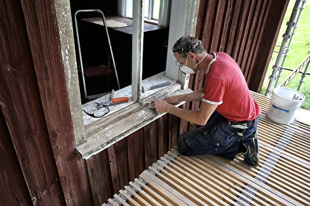26 juli 2017 - Roger från Krokfors Finsnickeri renoverar fönstren, bågarna renoveras i snickeriet i Krokfors och karmarna renoveras på plats i Långelanda. Skadat och ruttet trä åtgärdas, därefter behandlas karmarna med olja och grundfärg. Slutligen ska fönstren målas med en vit nyans som ska överensstämma med den ursprungliga färgen.