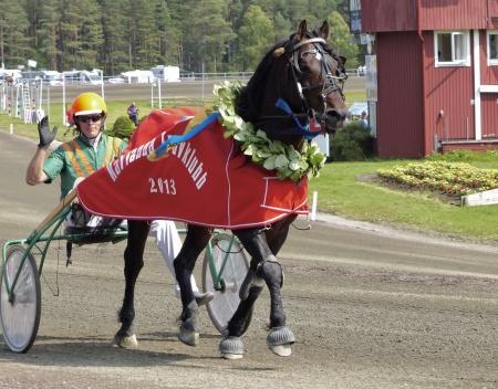 Vinnande ekipage i Erik Perssons Memorial blev Raggmunken med kusken Conny Gustafsson. Här med Karlanda Travklubbs lagerkrans och hederstäcke.