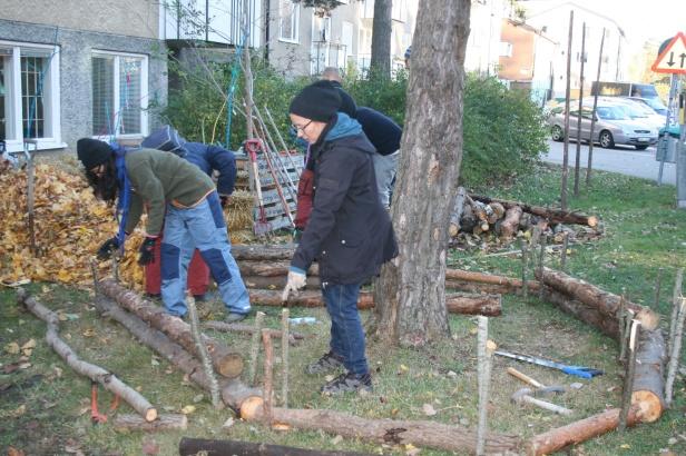 Bygga med lokala material. Här används grenar och löv för att bygga rabatter.