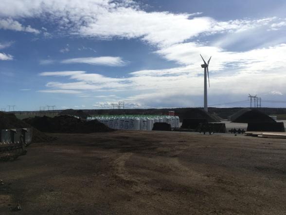 Jord, sten, kol, kross, gödsel, himmel, vindkraftverk och asfalt.