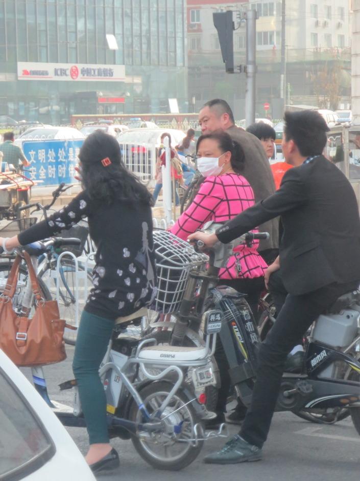 Luften i Peking är dålig, många använder munskydd för att skydda sig. Att använda hjälm för att skydda sig mot potentiella trafikolyckor verkar inte lika högprioriterat.