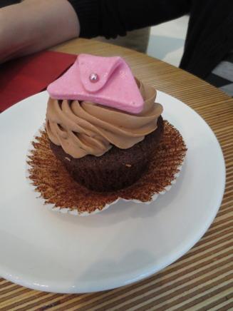 En gullig och god cupcake från caféet, dekorerad med en handväska på toppen.