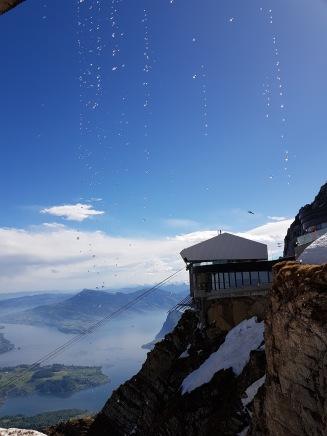 Utsikten från Mount Pilatus. Härliga vyer i solskenet medan smältvatten från snön droppar ner