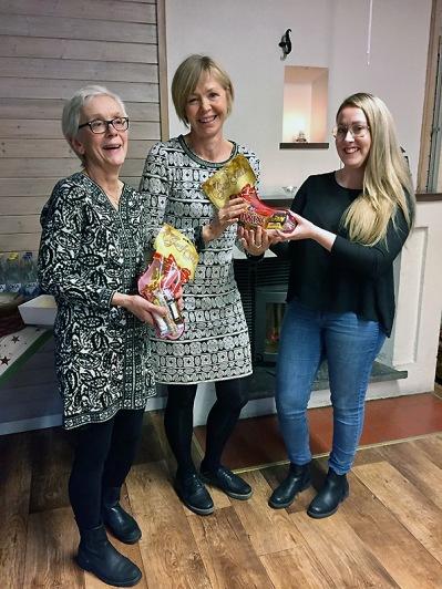 Jullunchen innehöll också en liten frågetävling. Här delar Linnea ut vinsten till Kerstin & Gunilla, som vann tävlingen.