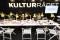 Syntolkning: Kulturrådets utställarplats, långt bord med en rad gula lampor uppställda på rad. Foto: José Figueroa