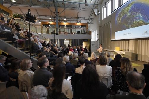 Syntolkning: Stor publik lyssnar på seminarium.