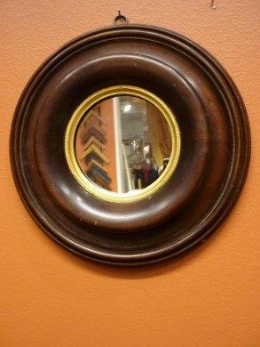 Svarvad ram i valnöt med förgylld inkant. Kvicksilverglas.