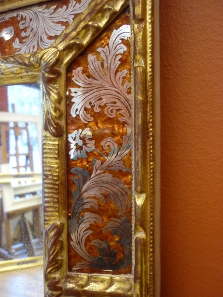 Förgylld spegel. Detalj av ramglaset och dess framskrapade mönster