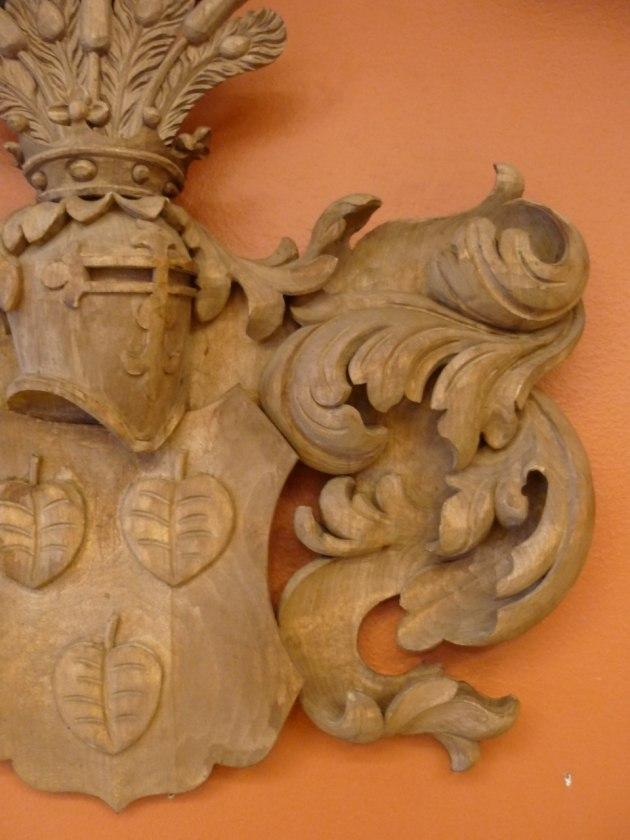 Vapensköld bestående av sköld, tunnhjälm med krona för uradel, hjälmtäcke samt hjälmprydnad.