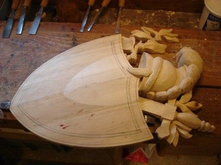 Handskuren träsköld med romersk hjälm och svärd