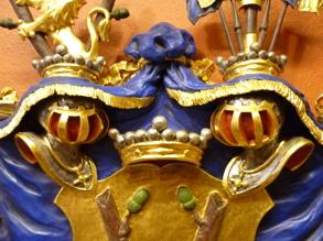Hjälmar samt friherrekrona omgivna av hjälmtäcke