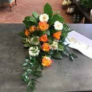 Liggande sorgbukett i orange och vitt