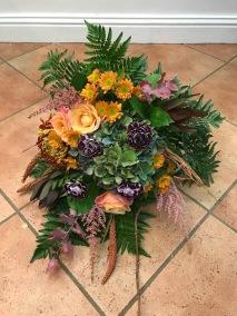 Liggande sorgbukett orange och lila