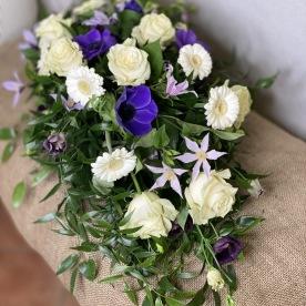 Liggande sorgdekoration i lila och vitt