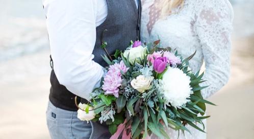 bröllopsbild på ett brudpar med vacker blombukett