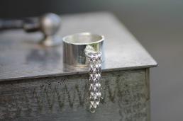 Ring i 925silver med 3 st ärtlänkar hängande i ring. Bredd ringskena 10 mm - 1.250 kr