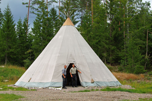 Tippi tältet som har en stor grill i mitten och som rymmer många ätande gäster.