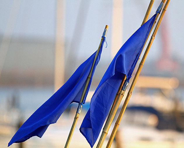 Snipan på andra sidan bryggan sattsar på fiske med nya flaggor till vakarna.