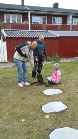 James, Mats och Tuva jobbar med att lägga ut fina stenar upp till lekstugan.