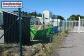 Mörkgrönt industristängsel med taggtråd