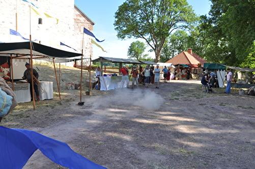 Här inviger jag en medeltidsmarknad på Kastelholms slott på Åland, med min lilla svartkrutskanon (lilla svarta pricken vid flaggstolpen). Fotografen har lyckats fånga själva svartrökspuffen på bild.