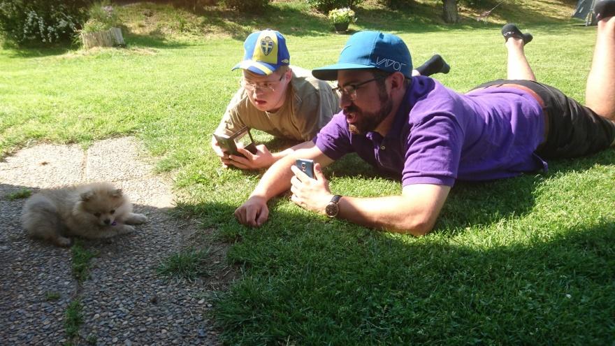 Medlem och personlig assistent ligger på en gräsmatta och fotograferar en liten hund.