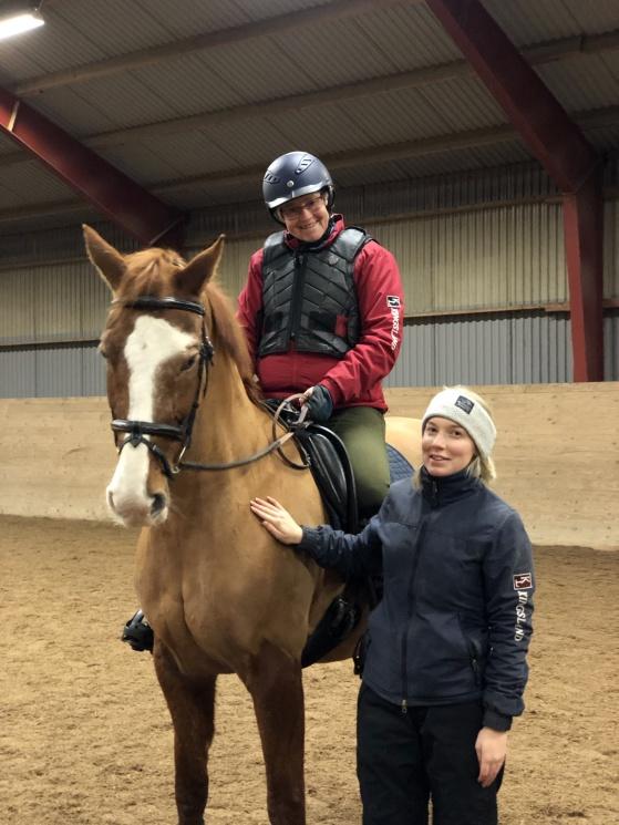 Medlem rider på brun häst i ridhus, assistent står vid sidan