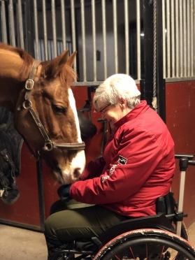 Kvinna sitter i rullstol framför sin häst i stallet