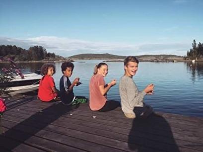 Happy children enjoying icecream treats on the dock in the beautiful summers eve sunshine!