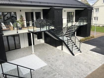 Tre svarta aluminiumtrappor med glasräcken