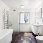 Rymligt helkaklat badrum med dusch och badkar
