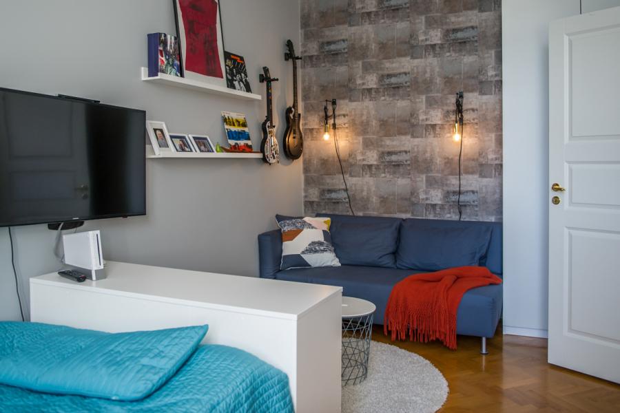 Tonårsrum med soffhörna och TV som kan vridas både mot sängen och soffan. Tapet med industriell känsla