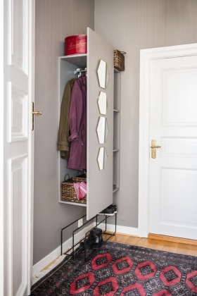 Platsbyggd hallmöbel som döljer ytterkläderna, och ger plats för korgar och spegel. Perfekt i en liten hall med 3 dörrar och begränsad väggyta. Att måla den i samma färg som väggen gör att den tar ännu mindre plats.