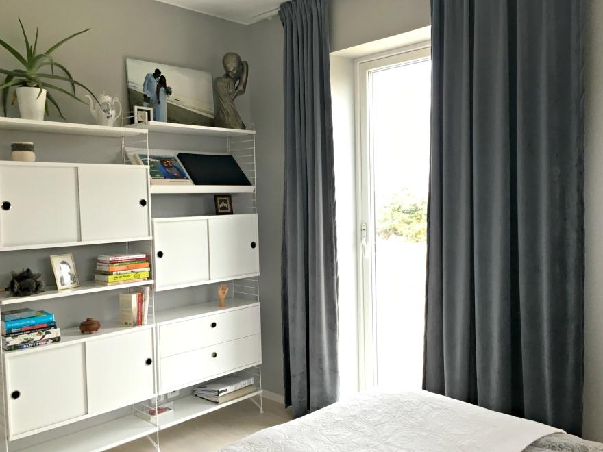 Sovrum med String hyllkombination, sammets gardiner.
