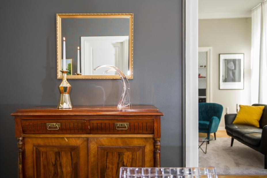 Varmgrå vägg framhäver det vackra skåpet, blanda gammalt och nytt