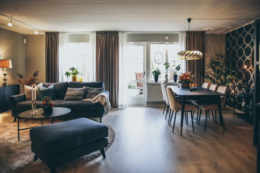 Vardagsrum i Varberg. Myhres & Coey renoverade med varma färger, smart och behaglig belysning, samt en stor skön matta gör rummet ombonat.