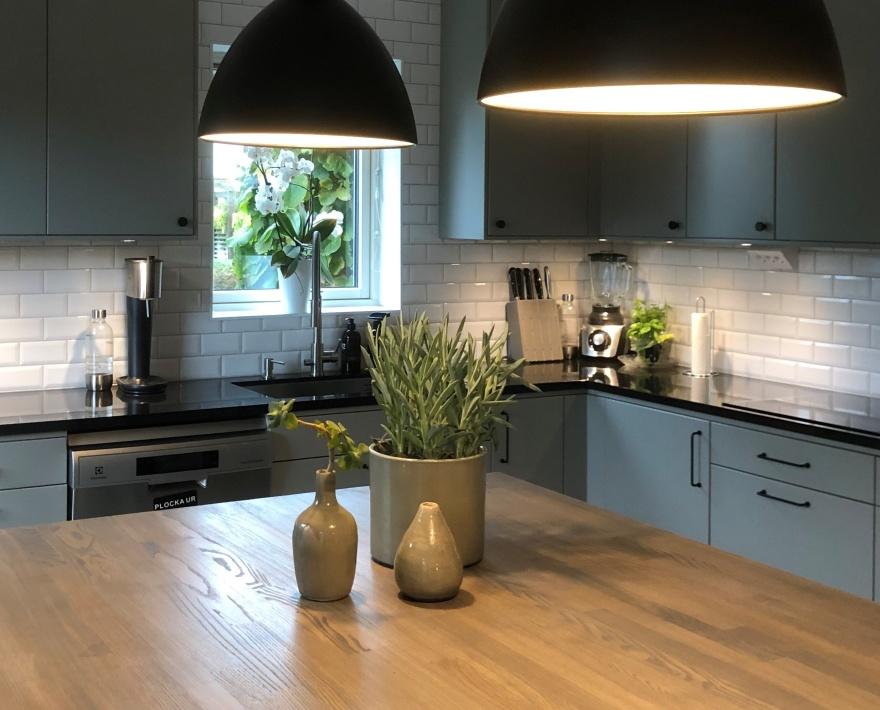 Kök med luckor i en varm mörkgrå färg och stor köksö