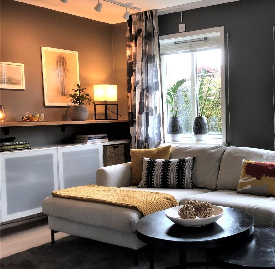 Mörka väggar och bra belysning ger ett mysigt krypin i vardagsrumsdelen