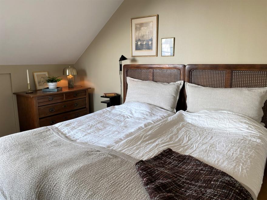 Sovrum med varma färger och en blanding av nya och ärvda möbler.Design och planering av Myhres & Coey.