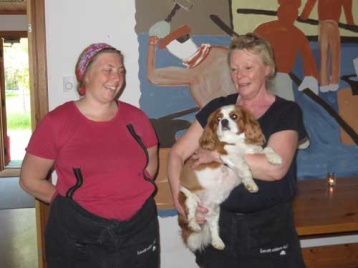 """Från.vänster. Fia Fengberg och Elisabeth """"Bettan"""" Johannesson med vovve Sluggo. De två förstnämnda gjorde en mycket god 3-rätters middag på plats i det lilla köket till oss matsugna mc-åkare vid Furudals Bruk."""
