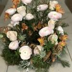 Dekorativ stående urnkrans med ranunkel och rosor